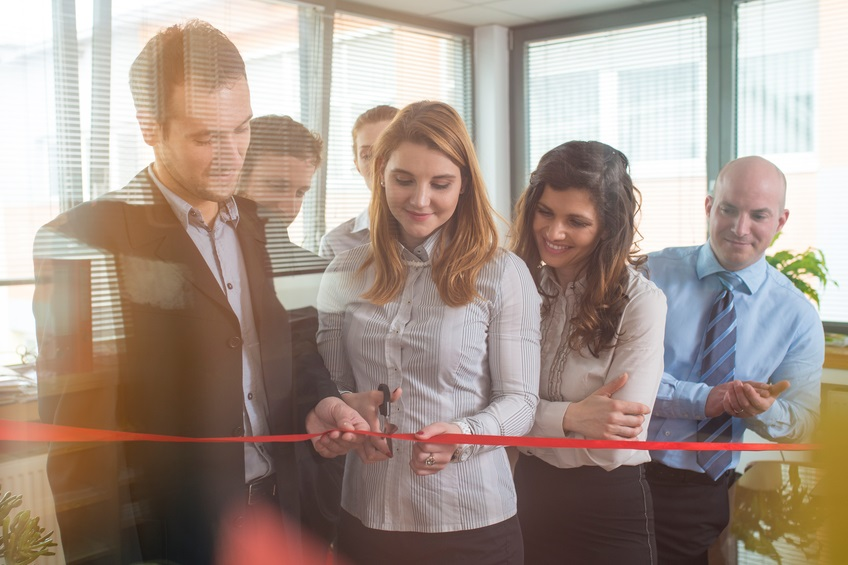 Businesspeople in the office. Woman is cutting a red ribbon with scissors, man is helphing her to hold it, other people are applauding. They are all happy with smile on their faces. Shot through glass.